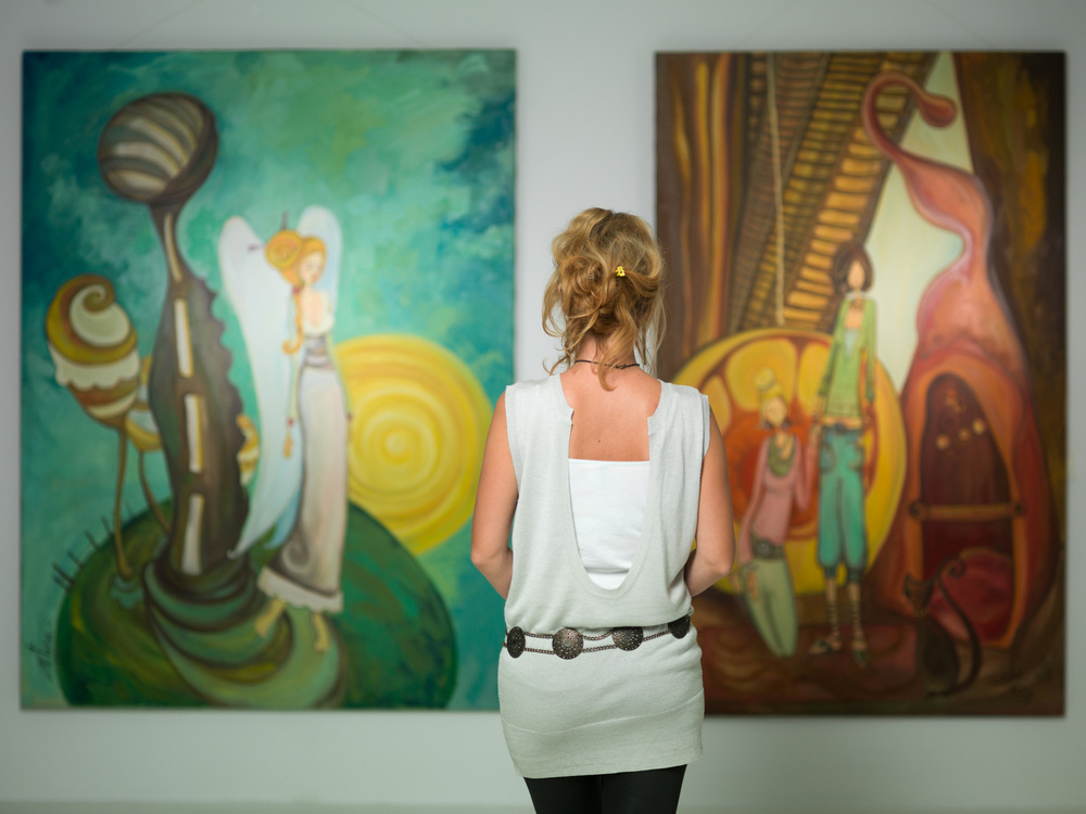 woman staring at gallery art - Home